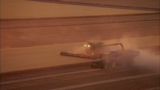 AERIAL Farm machinery harvesting wheat with blowing dust near Wilcox, Arizona, USA