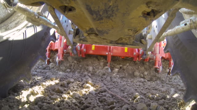 pov farm machinery ploughs furrows in field, uk - plough stock videos & royalty-free footage