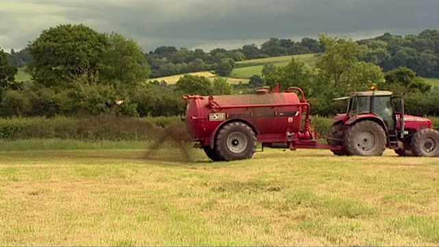 Farm machinery spraying fertiliser and manure onto field
