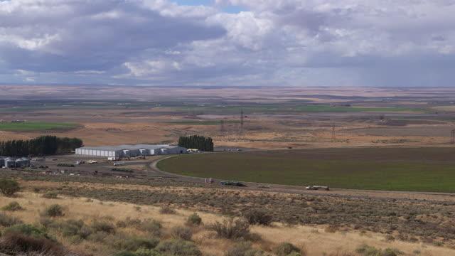 farm vista w tanker truck driving toward warehouse - wiese stock videos & royalty-free footage