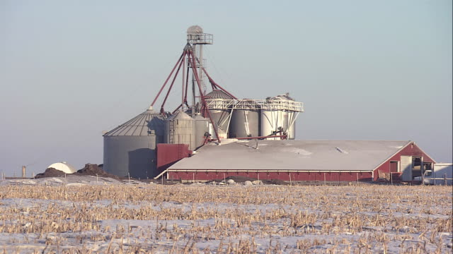 WS Farm with silos and red barn, with snow on the ground / Iowa, United States