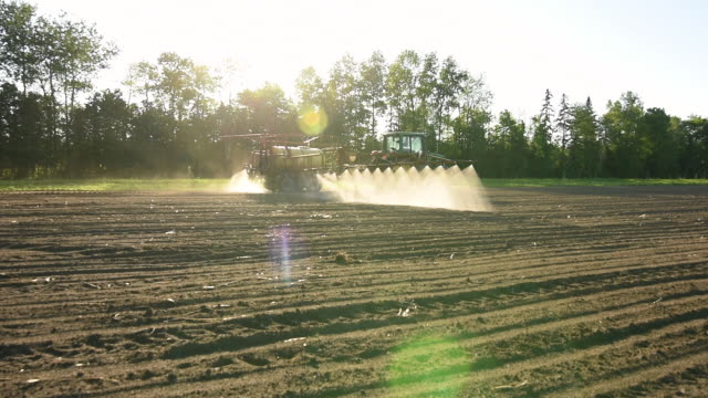 farm worker in tractor watering new crops. - ontario canada stock videos & royalty-free footage