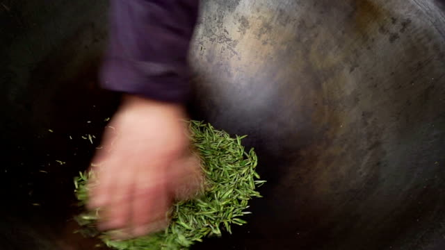farm worker stir frying tea in chinese traditional way in steel pan. - chinese tea pot stock videos and b-roll footage