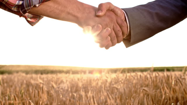 SLO MO Farmer and businessman shaking dusty hands