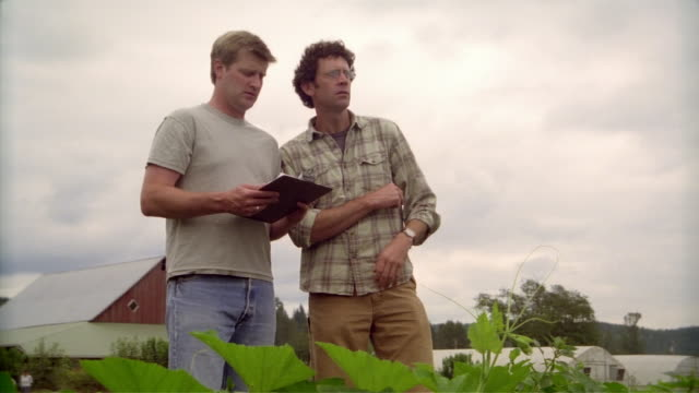 Farmer and man with clipboard examining field