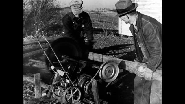 farmer and son at the electric saw / pass a log through the machine / cu of blade going through wood farmers use the electric saw on january 01 1940... - 1940 stock videos & royalty-free footage