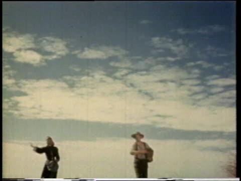 1941 ws farmer and wife sowing a field and farmers walking across fields / united states  - hängslen bildbanksvideor och videomaterial från bakom kulisserna