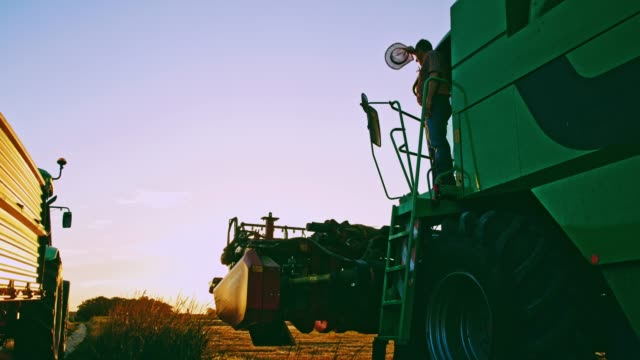 farmer climbing down from combine harvester in rural field,slow motion - tractor stock videos & royalty-free footage