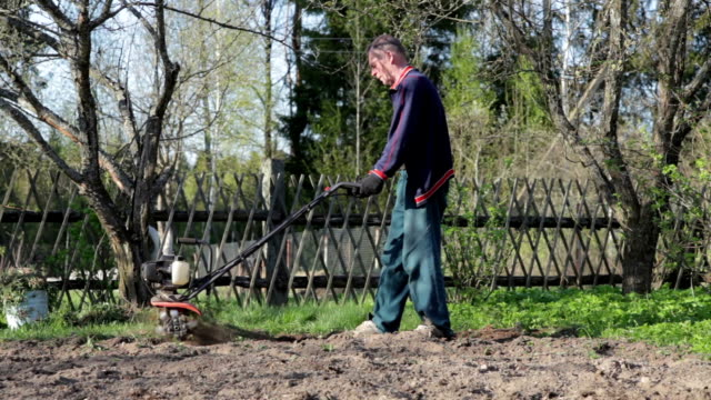 Farmer cultivating the ground with the garden tiller