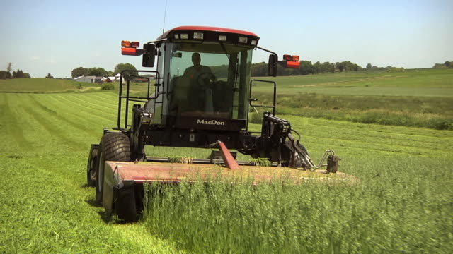 ws ts slo mo farmer cutting and conditioning organic hay field / columbus, wisconsin, usa - hay stock videos & royalty-free footage