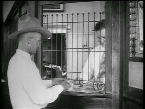 b/w 1928 farmer depositing money at teller's window at bank / oklahoma / newsreel - 1928 stock videos & royalty-free footage