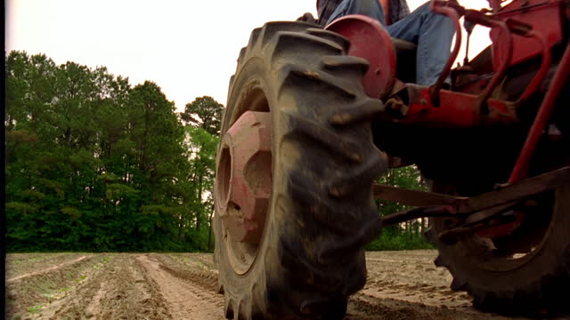 A farmer drives a tractor across a dirt field.