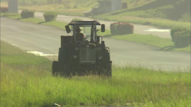 a farmer drives a tractor over a grassy hill. - animale femmina video stock e b–roll