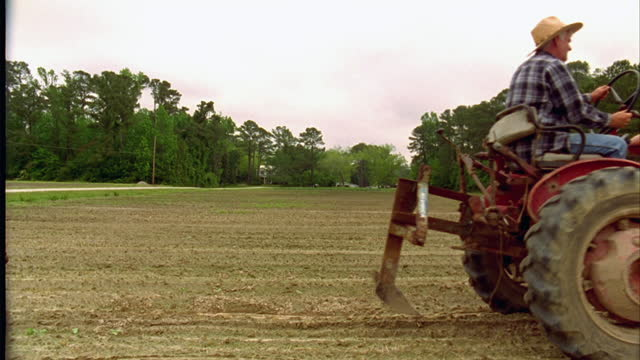 A farmer drives a tractor over an empty field.