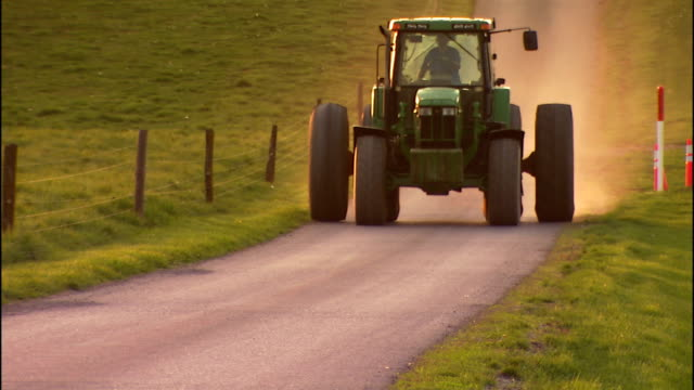 a farmer drives a wide tractor on a rural road. - tractor stock videos & royalty-free footage