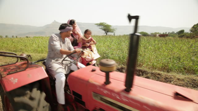 Farmer driving a tractor with his family in a farm