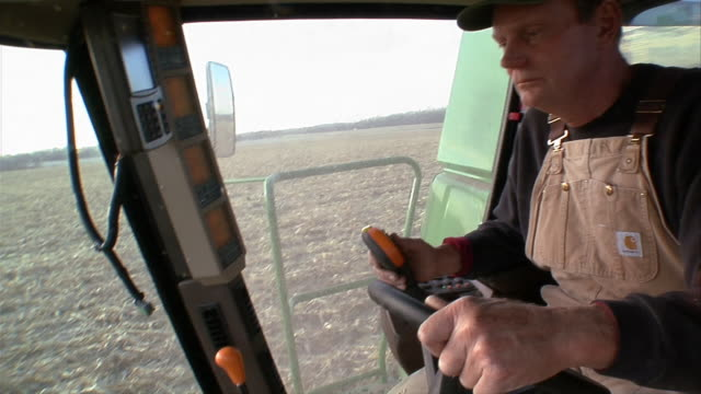 ms farmer driving harvester through cornfield/ manchester, michigan - baseballmütze stock-videos und b-roll-filmmaterial