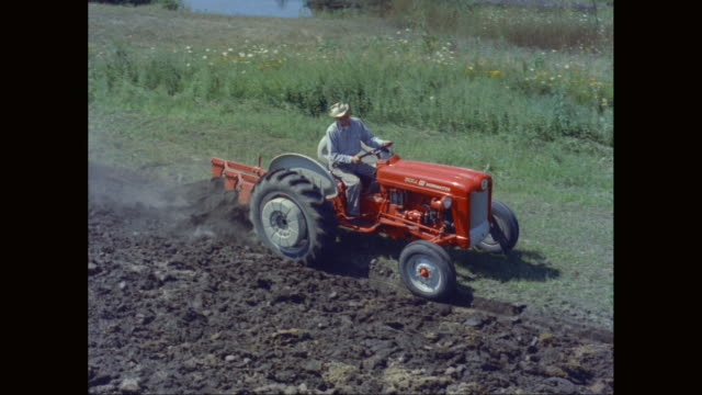 ws ts farmer driving tractor while roller harrow ploughing in field / united states - harrow agricultural equipment stock videos & royalty-free footage