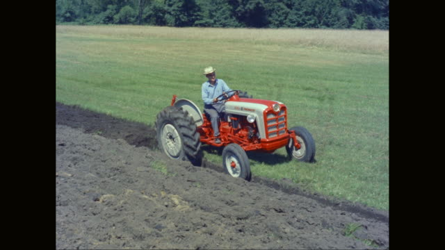 ws ts farmer driving tractor while roller harrow ploughing in field / united states - plough stock videos & royalty-free footage