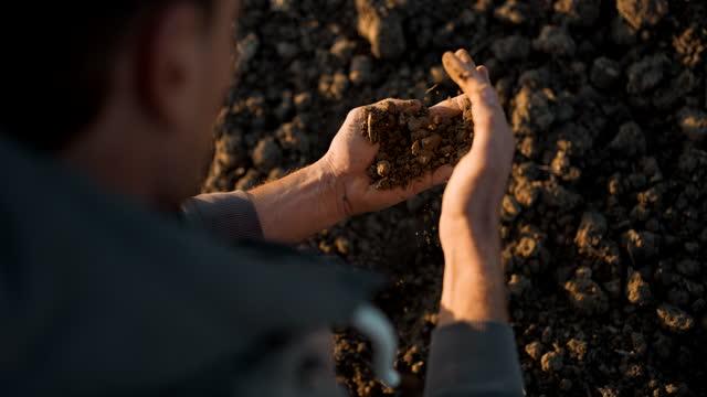 vídeos de stock e filmes b-roll de slo mo farmer examining soil on a field - solo