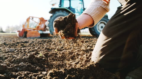 slo mo farmer examining the soil - tractor stock videos & royalty-free footage