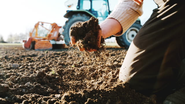 slo mo farmer examining the soil - tractor stock videos & royalty-free footage