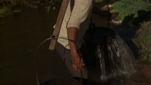 ms farmer filing two buckets with water from stream, weishan, yunnan, china - bucket stock videos & royalty-free footage