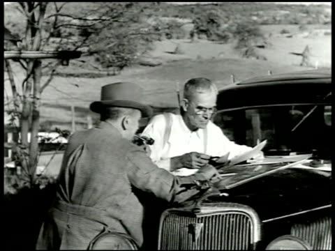 vidéos et rushes de farmer filling out papers outside on car hood mot 1943 cu paperwork 'farm manpower inventory 1943' farmers walking toward large farm house wwii... - 1936
