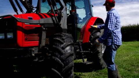 hd crane: farmer getting into tractor cab (farm agriculture) - tractor stock videos & royalty-free footage