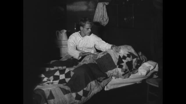 vidéos et rushes de farmer getting young adult boys out of bed cu rooster boys feeding milking cows into bucket cu calf feeding suckling cow straining milk can w/... - 1936