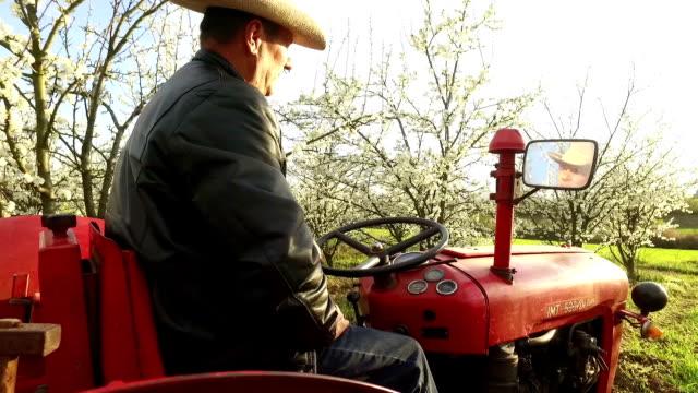 Agricoltore attraversando una fattoria su un trattore