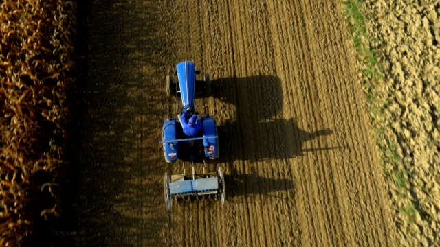 stockvideo's en b-roll-footage met aerial farmer harrowing a field - tractor