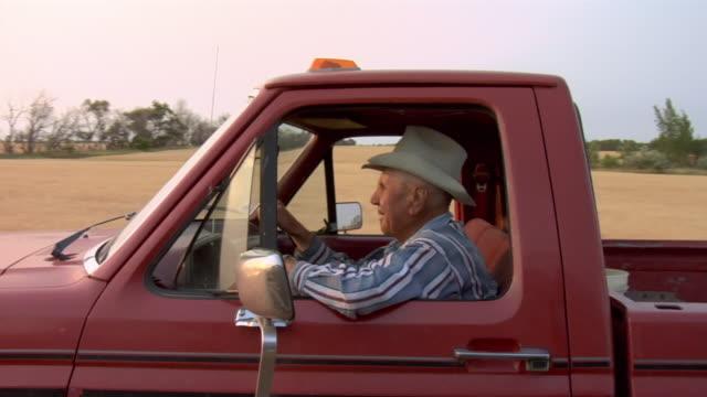 A farmer in a cowboy hat drives a pickup truck through a golden field.