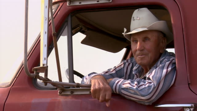 A farmer in a cowboy hat sits in his pickup truck smiling.