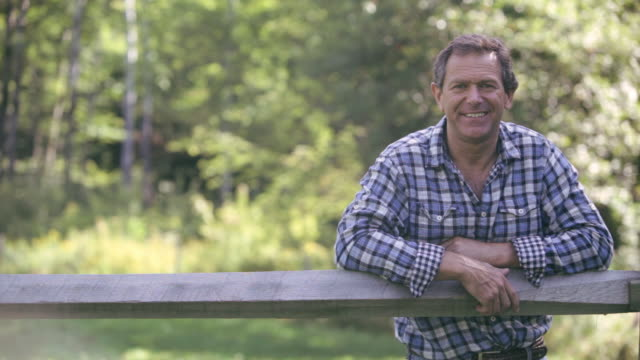 vidéos et rushes de  ds farmer leaning against a fence, smiling / stowe, vermont, united states - s'appuyant