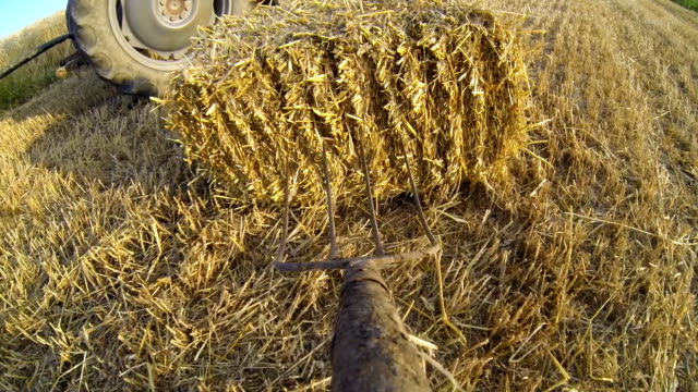 slo mo farmer loading bale on a trailer - garden fork stock videos & royalty-free footage