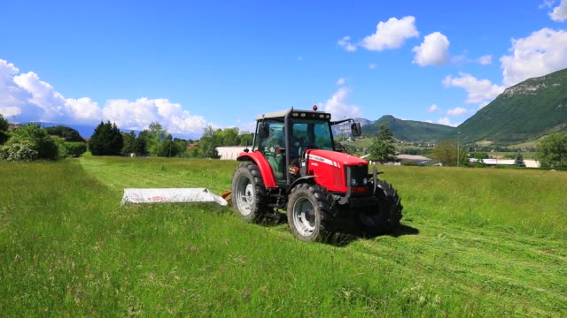 vidéos et rushes de farmer mowing a field in a tractor during the lockdown period due to the fight against covid19 outbreak on may 6, 2020 in les marches, france. - foin