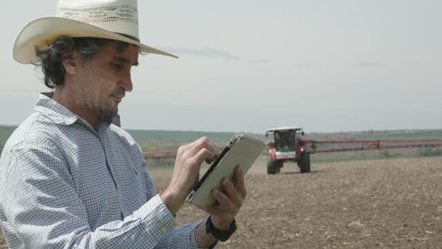 農夫は、デジタルタブレットで作物の噴霧器を操作します。 - remote control点の映像素材/bロール