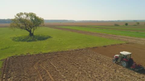 vídeos y material grabado en eventos de stock de aerial farmer arar un campo con un tractor - campo arado