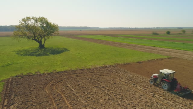vídeos y material grabado en eventos de stock de aerial farmer arar un campo con un tractor - tractor