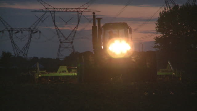 LA CU MS PAN Farmer plowing field at dusk, Newark, Illinois, USA
