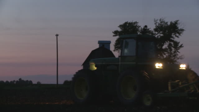 MS Farmer plowing field at dusk, Newark, Illinois, USA