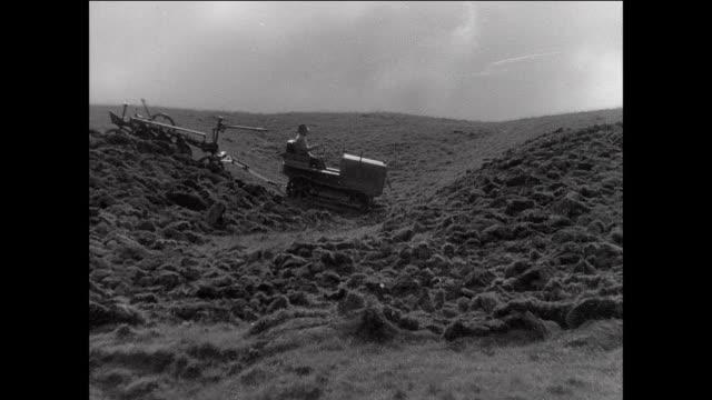 montage farmer plowing large field on tractor / aberystwyth, wales - 1931年点の映像素材/bロール