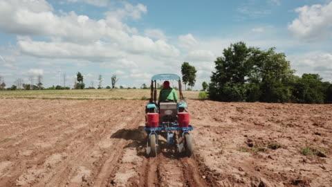 vídeos y material grabado en eventos de stock de agricultor arado el campo y turbina eólica sobre el fondo, maquinaria agrícola - campo arado