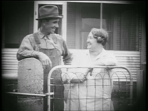 b/w 1928 farmer + plump wife smiling + hugging by gate of house / oklahoma / newsreel - 1928 stock videos & royalty-free footage