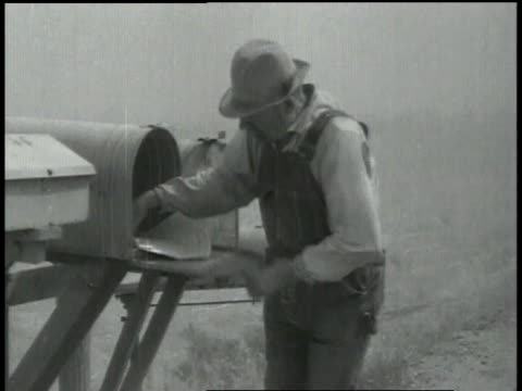 farmer removing mail from a mailbox / farmer holding his hat in dusty windy conditions - dust bowl stock videos and b-roll footage