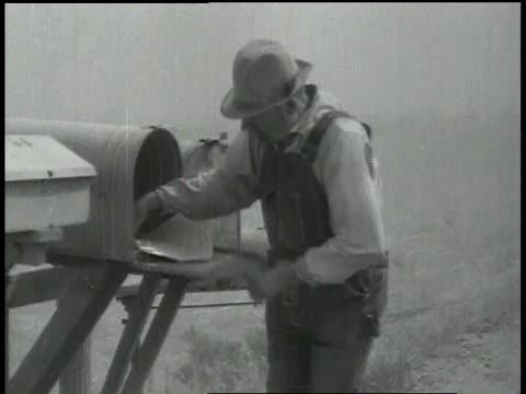 vídeos y material grabado en eventos de stock de farmer removing mail from a mailbox / farmer holding his hat in dusty windy conditions - vendaval de polvo