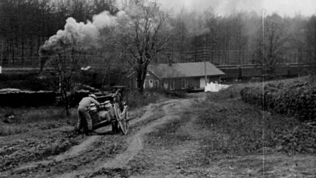 farmer repairs wheel on cart / wagon train passes by behind farmer - anno 1916 video stock e b–roll