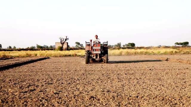 vídeos y material grabado en eventos de stock de tractor de montar a caballo del granjero en el campo - operar