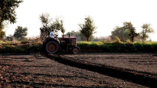farmer riding tractor in the field - plowed field stock videos and b-roll footage